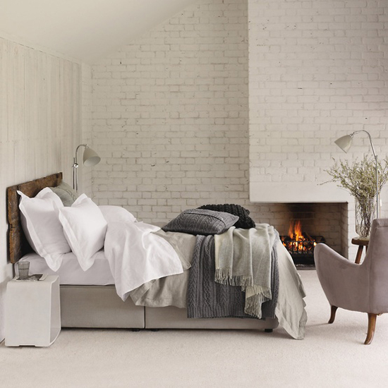 neutral-texture-bedroom-white-brick-fireplace-gray-wood-bed
