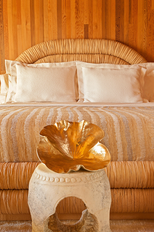 Kelly Wearstler beach house bedroom wood paneling round headboard gold clam shell