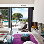 Portugal mod summer home, Nuno Benito, contemporary living room, concrete fireplace hearth, poufs, cowhide chair, magenta rug