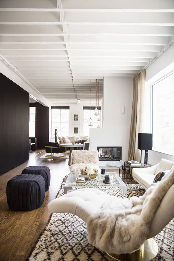 nate-berkus-jeremiah-brent-domino-rita-hazan-apt-living-room-neutral-glam-black-white-brass-1970s-beni-ourain-Lucite-table