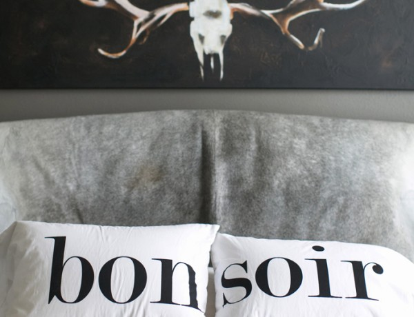 Erika Brechtel home bedroom cowhide headboard antlers painting bon soir pillows fur throw photo by Bryce Covey
