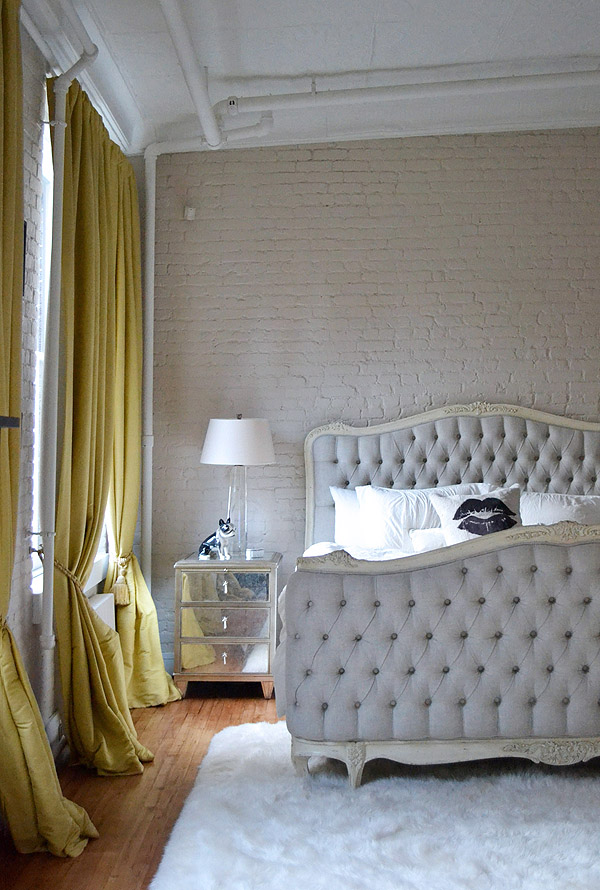 Soho NYC loft Tamra Sanford bedroom brick walls tufted bed mirrored nightstand