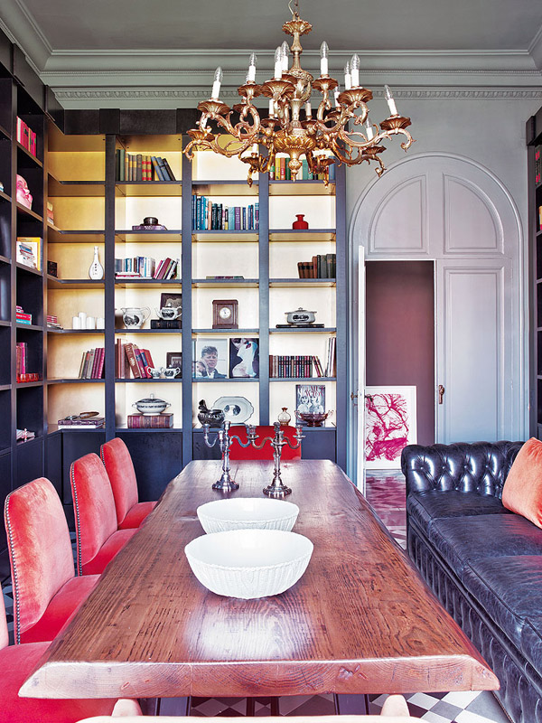 colorful classic Barcelona dining room gold backed bookshelves red velvet chairs tufted chesterfield sofa chandelier wood table