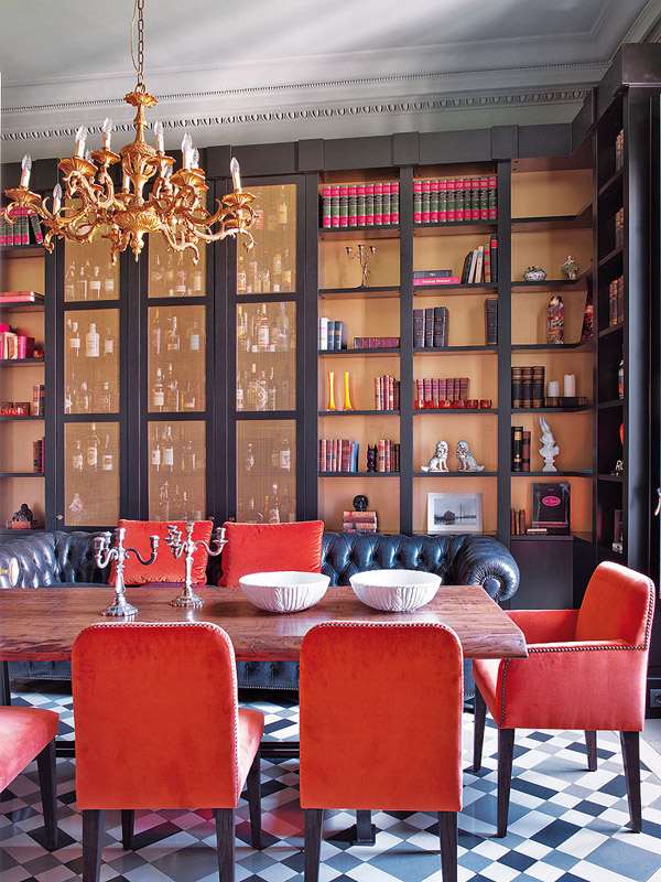 colorful classic Barcelona dining room gold backed bookshelves red velvet chairs tufted chesterfield sofa chandelier