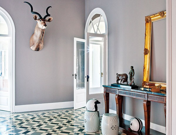 colorful classic Barcelona entry horn stools tiled floor gilded frame gray walls