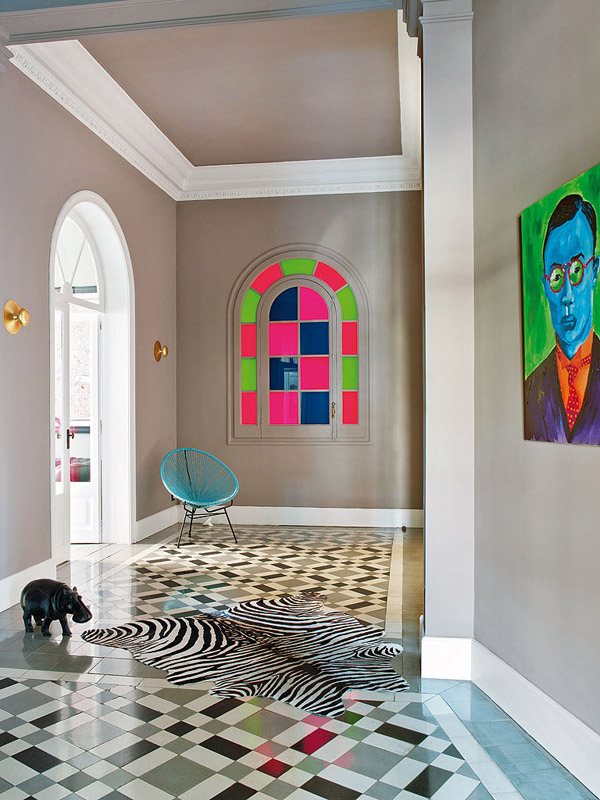 colorful classic Barcelona hallway tiled floor gray walls zebra rug bright stained glass modern art