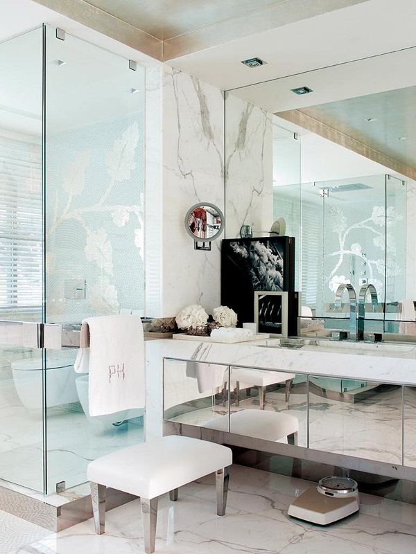contemporary glam in Portugal bathroom white carrera marble mirrored cabinets