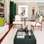 contemporary glam in Portugal living room green doors skull art French bergere chairs black horn table