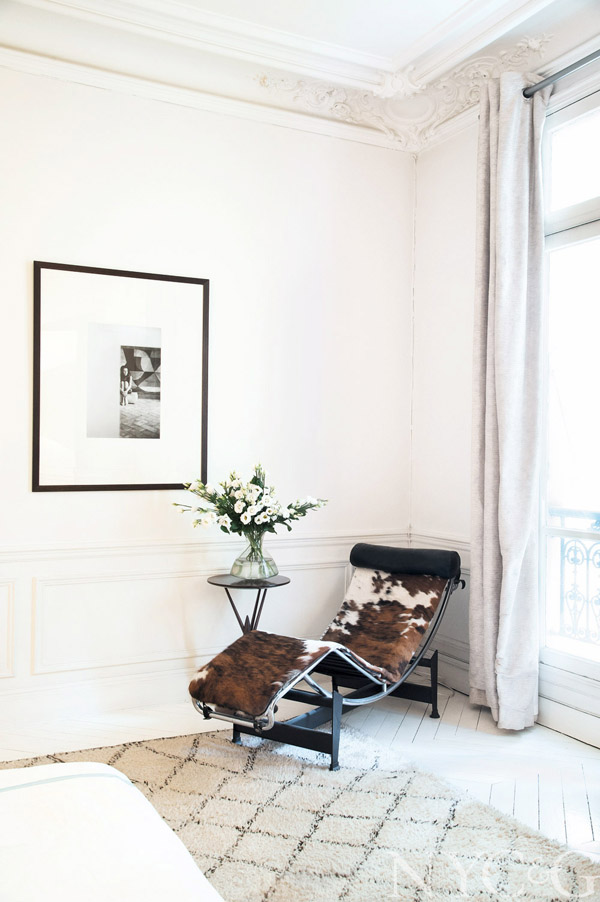 photographer apt in paris Stephane Kossmann bedroom cowhide lounger white paneling painted floor beni ourain rug balcony