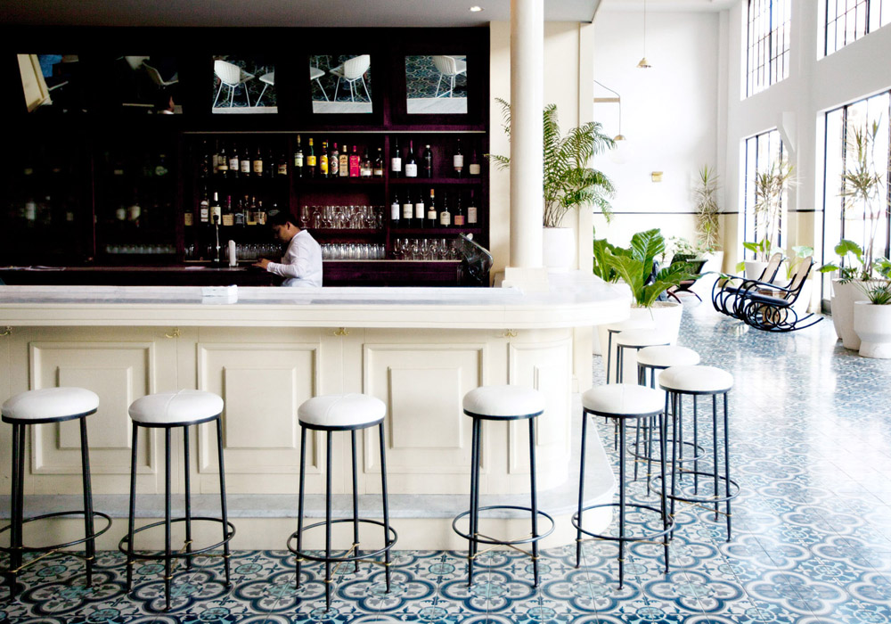 American Trade Hotel Panama City by Commune Design bar patterned tile floor white stools