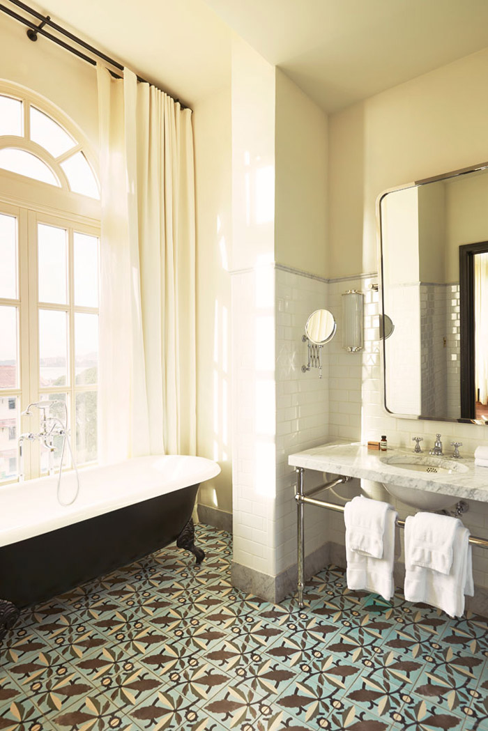 American Trade Hotel Panama City by Commune Design bathroom tiled floor marble sink claw foot tub
