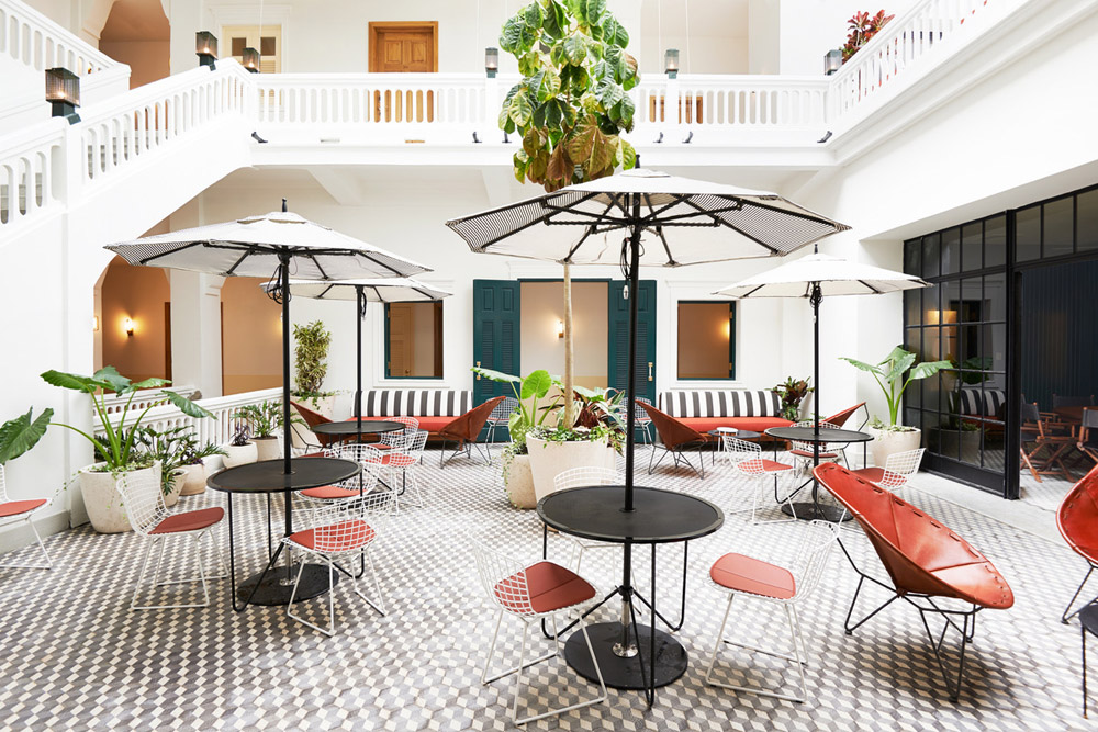 American Trade Hotel Panama City by Commune Design courtyard Bertoia chairs umbrellas striped benches