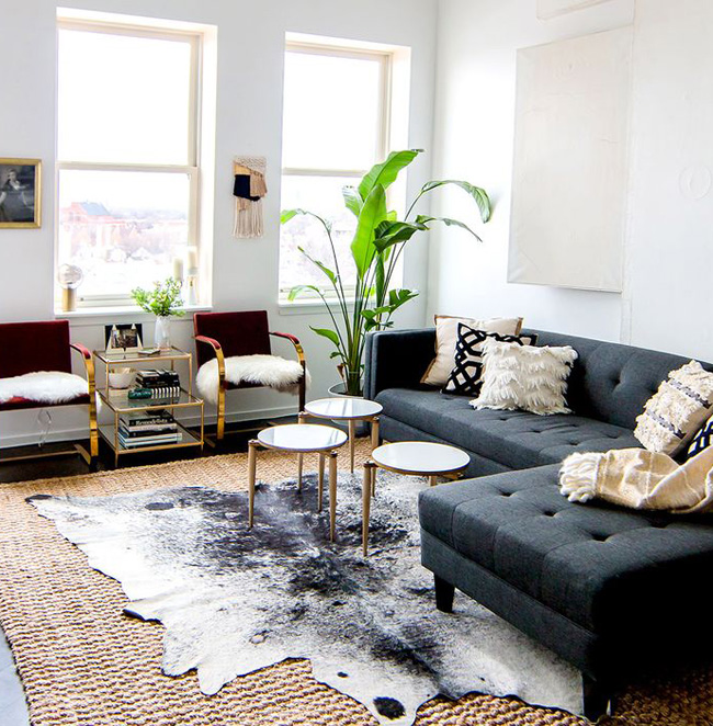 layering rugs cowhide over seagrass living room Shelby Girard via Domaine