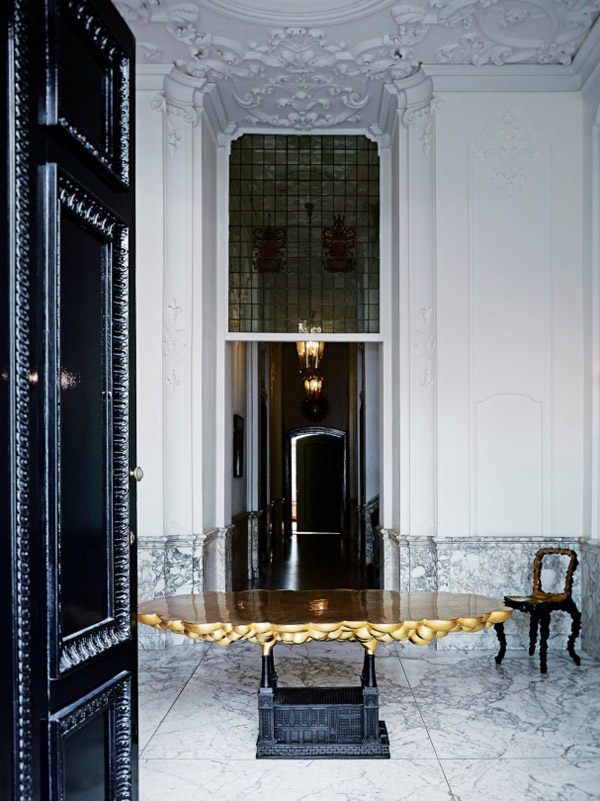 Viktor & Rolf Amsterdam HQ entry black door gold table white marble wainscot floor