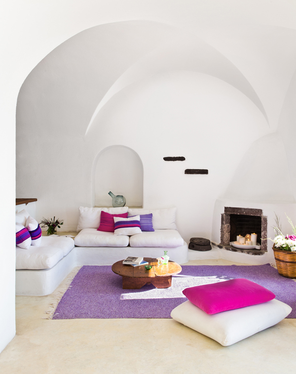 Greece Cyclades Oia interiors architecture Perivola Suites living room white minimalist purples fireplace