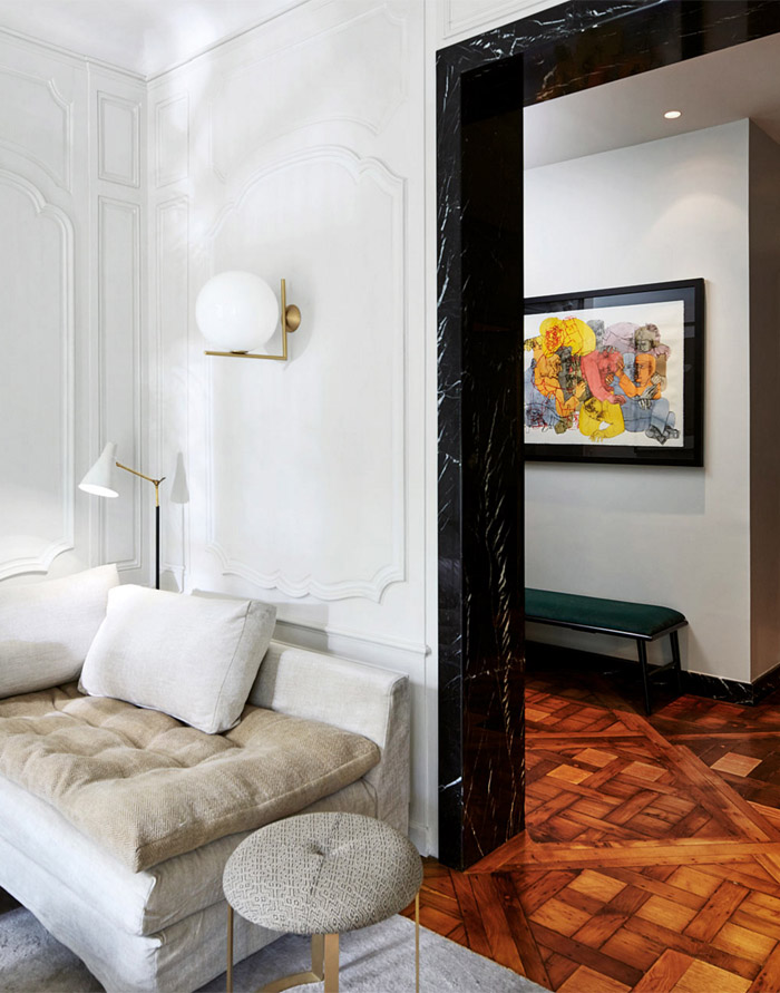 parisian-glam-laura-gonzalez-living-room-detail-white-molding-walls-parquet-wood-floors-black-marble-doorframe