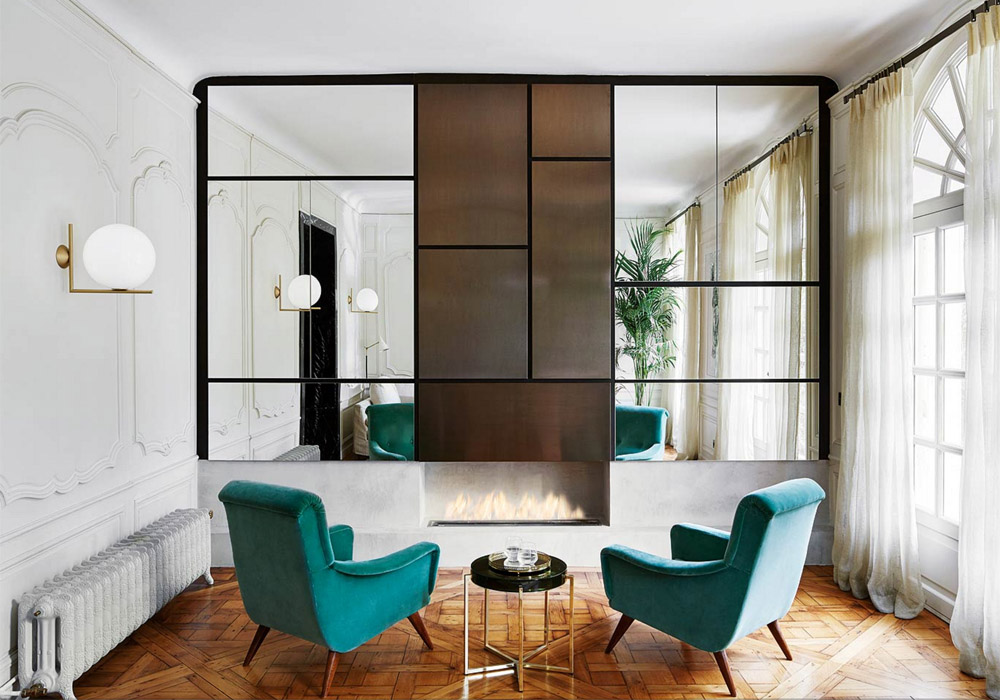 parisian-glam-laura-gonzalez-living-room-teal-velvet-armchairs-wood-parquet-floors-brass-sconce-mirrored-wall-moldings-fireplace